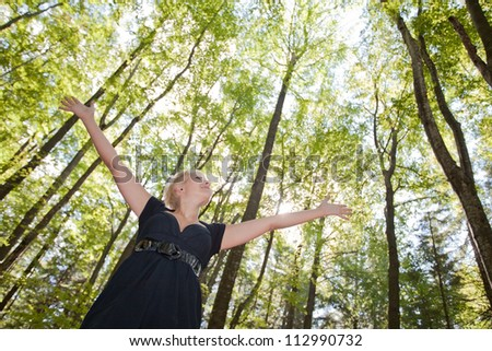 Young woman with arms raised enjoying  in green forest - stock photo