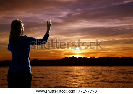 Young woman with arms raised in praise worshiping at sunset - stock photo