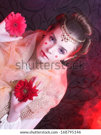 Young woman with artistic visage and hairstyle with red flowers