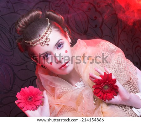 Young woman with artistic visage and hairstyle with red flowers - stock photo