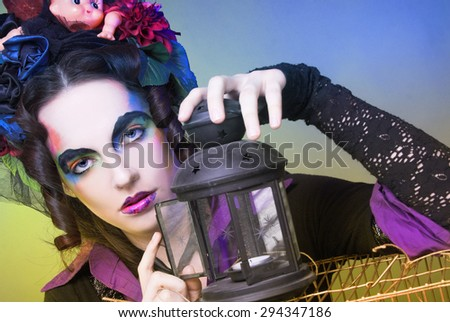 Young woman with artistic visage and with original hairstyle with dolls and flowers. - stock photo