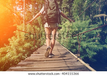 Young woman with backpack balancing across hanging bridge in tropical forest (intentional sun glare) - stock photo