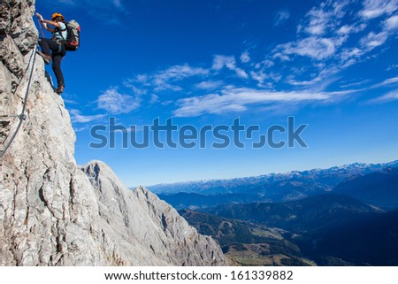 Young woman with backpack climbing high above mountain valley - stock photo