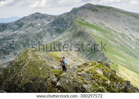Young woman with backpack do summer hiking in the mountains. Retezat, Carpathians, Romania. - stock photo