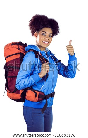 Young woman with backpack hitchhiking against a white background - stock photo
