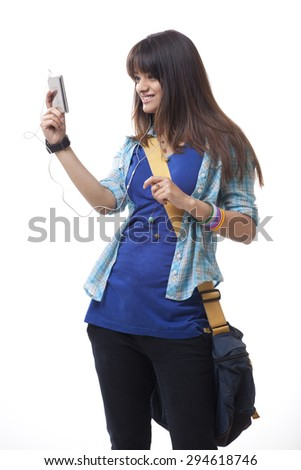 Young woman with backpack listening to music over white background