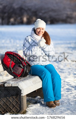 Young woman with backpack resting in winter park - stock photo