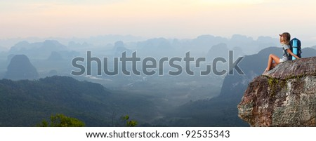 Young woman with backpack sitting on a cliff and enjoying a view - stock photo