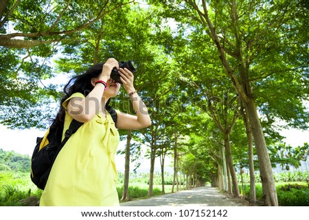 Young woman with backpack standing in the green forest taking photo - stock photo