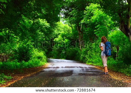 Young woman with backpack standing on a wet asphalt path in a park and looking to a trees - stock photo