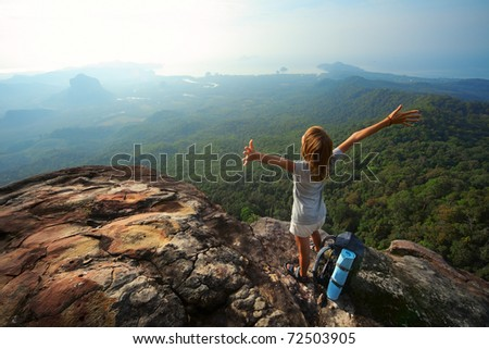 Young woman with backpack standing on cliff's edge and looking to a sky with raised hands - stock photo