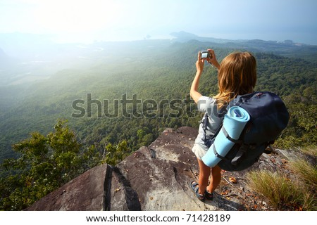 Young woman with backpack standing on cliff's edge and taking a photo - stock photo