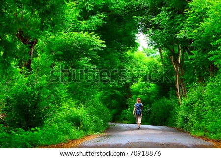 Young woman with backpack walking on a wet asphalt path in a park - stock photo