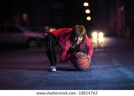 Young woman with basketball ball on night street - stock photo