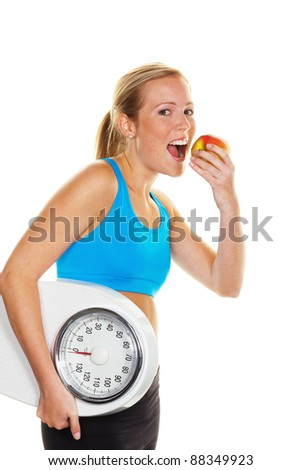 young woman with bathroom scale and apple. successful diet - stock photo