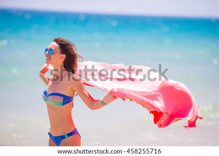 Young woman with beach towel during tropical vacation. Beautiful girl enjoy her summer holidays. - stock photo