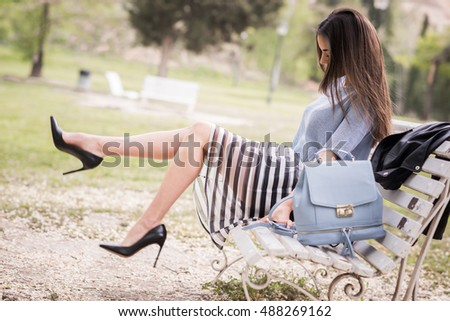 Young woman with beautiful legs in urban background wearing casual clothes. Girl wearing striped skirt and sweater sitting on a bench of an urban park