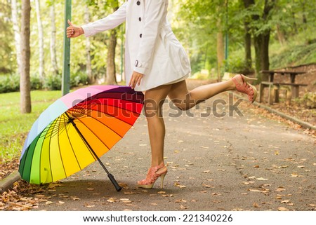 Young woman with beautiful legs standing in elegant dress. She is wearing glamorous high heels. She have a colorful umbrella. - stock photo