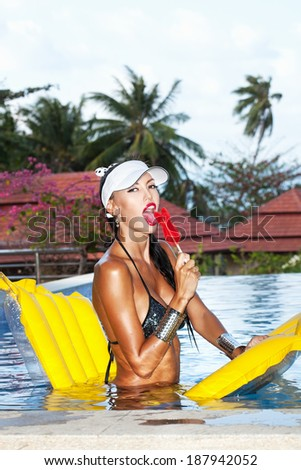 Young woman with beauty tanned body sitting on yellow air mattress in the pool in summer sucking lollipop and having fun . Outdoor fashion portrait of happy girl in white hat - stock photo