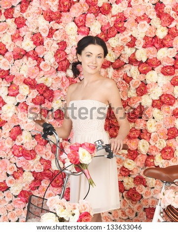 young woman with bicycle and background full of roses