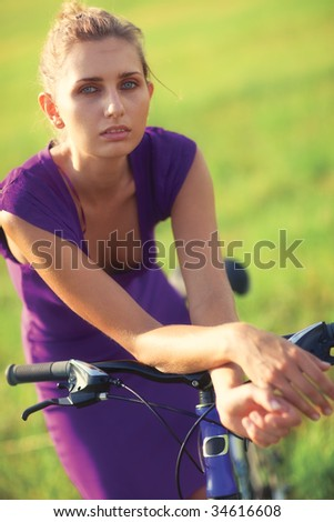 Young woman with bicycle at the field. Sunset light. - stock photo