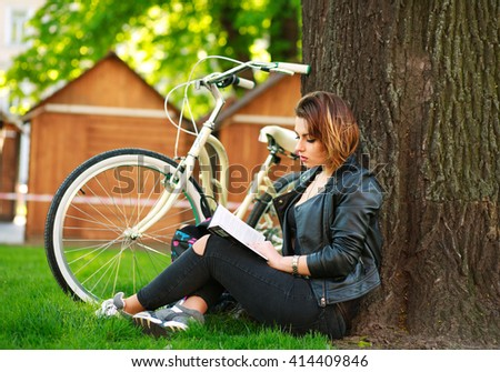 Young woman with bicycle reading a book in a city park on the grass - stock photo