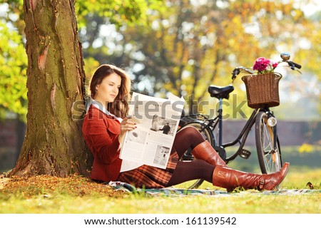 Young woman with bicycle sitting on a green grass and reading a newspaper in a park - stock photo