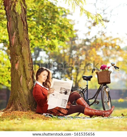 Young woman with bicycle sitting on a green grass and reading a newspaper in a park, shot with a tilt and shift lens - stock photo