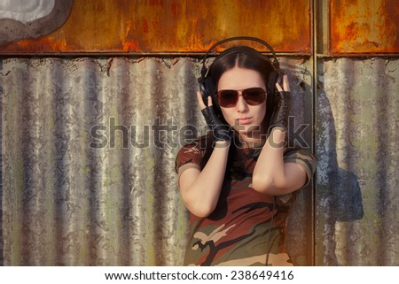 Young Woman with Big Headphones in Army Camouflage T-shirt - Portrait of a happy girl listening to music in a military fashion outfit  - stock photo