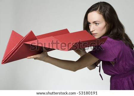 young woman with big paper airplane in her hands - stock photo