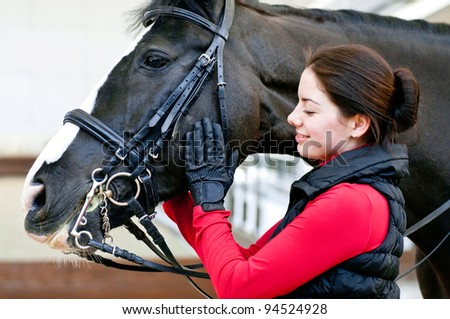 young woman with black horse - stock photo