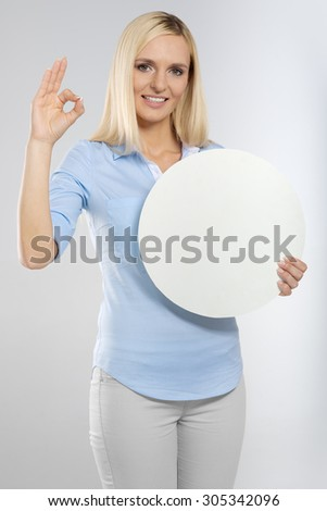young woman with blank circle board and showing okay gesture - stock photo