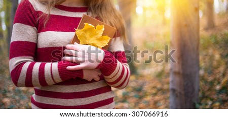 Young woman with book and yellow leaf relax in beautiful autumn park - stock photo