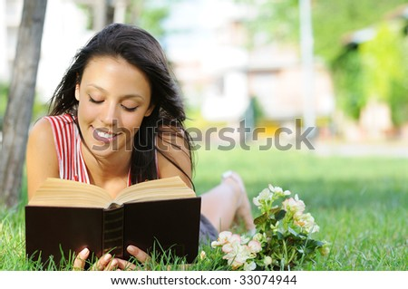 young woman with book, reading in green park