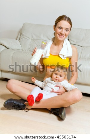 Young woman with bottle of milk exercising and her baby girl - stock photo