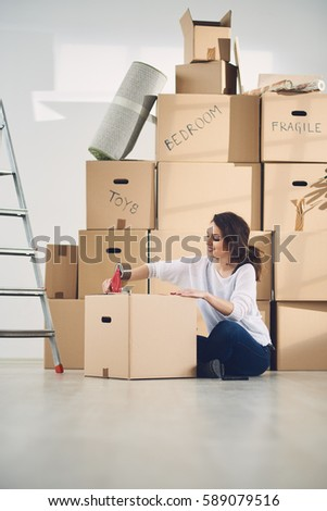 young woman with boxes moving in new apartment
