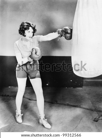Young woman with boxing gloves trains with a punching bag - stock photo
