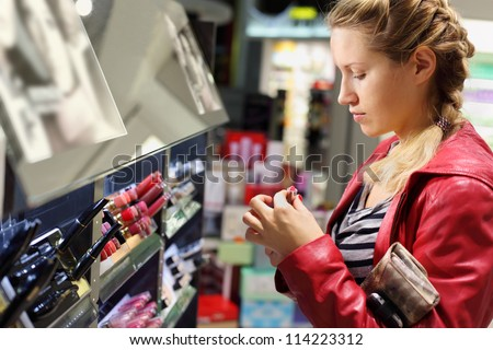 Young woman with braid chooses lipstick in small cosmetics shop. - stock photo