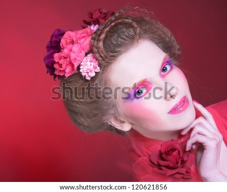 Young woman with bright artistic visage and with flowers in her hair