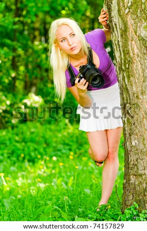 young woman with camera looking for object  - stock photo