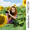 Young woman with camera - paparazzi hiding in the bushes sunflowers - stock photo