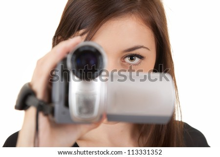 young woman with camera taking movie, white background - stock photo