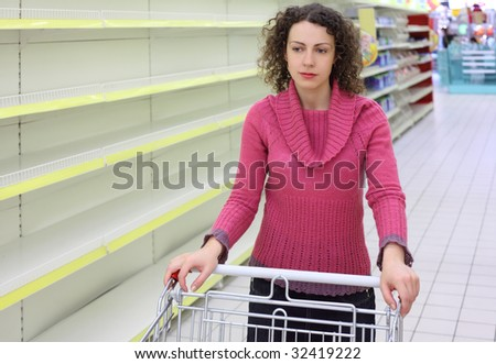 young woman with  cart in shop with empty shelves - stock photo