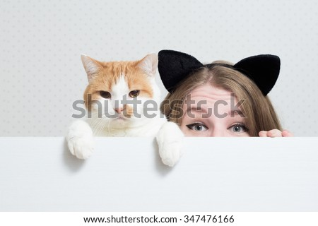 young woman with cat hiding behind a white banner - stock photo