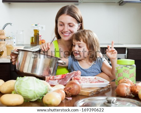 Young woman with child making soup from meat and vegetables at kitchen - stock photo