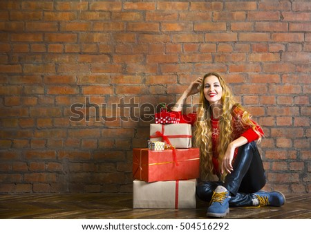 Young woman with Christmas gift near brick wall
