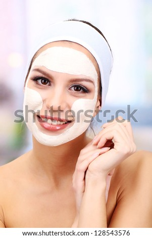 Young woman with clay facial mask, on bright background