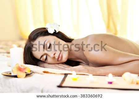 Young woman with close eyes getting massage in spa salon.