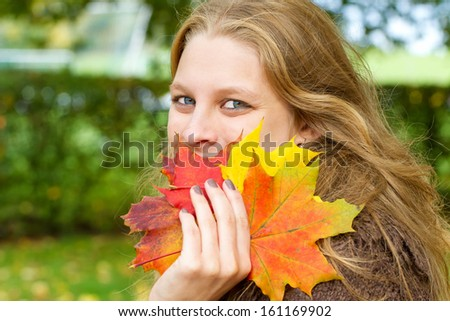 Young woman with colorful autumn leaves in her hand - stock photo