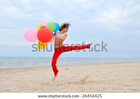 young woman with colorful balloons jumping on the beach - stock photo